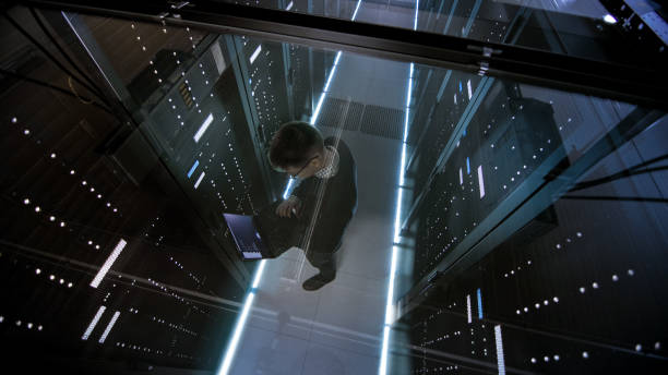 top view through the glass of it engineer working with laptop in data center full of  active rack servers. - computer network stock pictures, royalty-free photos & images