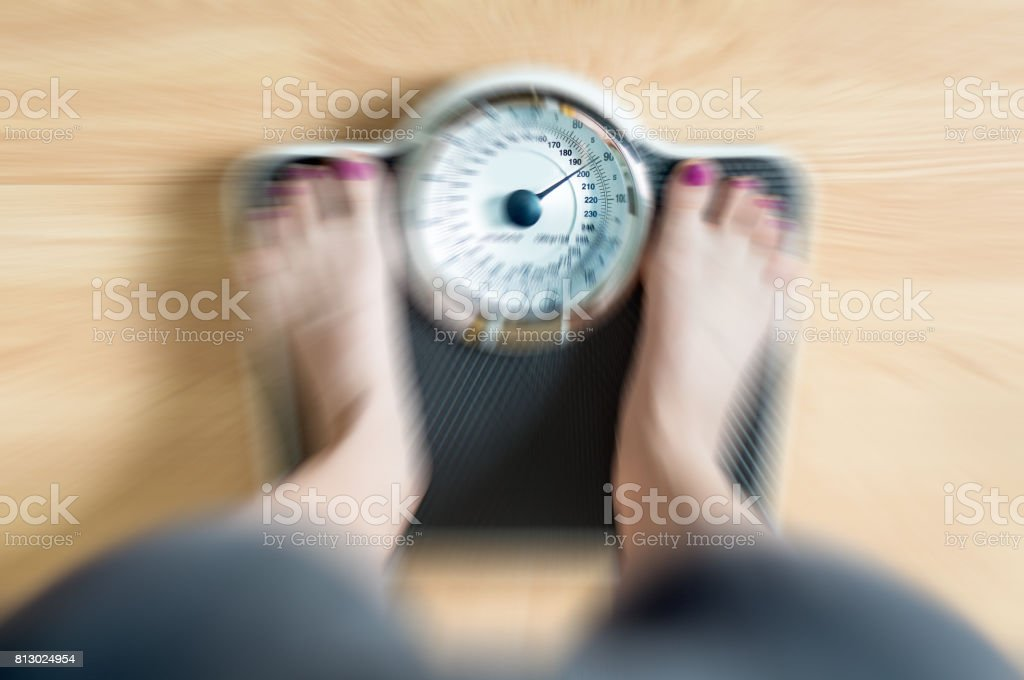 Top view to female feet on scale with dramatic blur zoom effect. stock photo