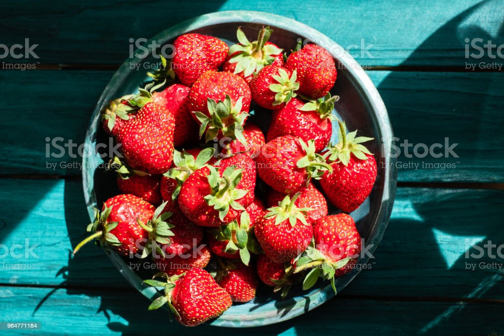 Top view to fresh strawberries in green plate on green wooden table royalty-free stock photo