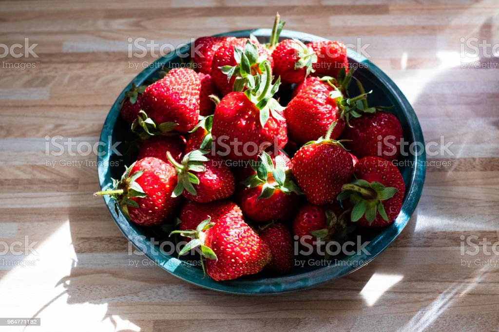 Top view to fresh strawberries in green plate on wooden table royalty-free stock photo