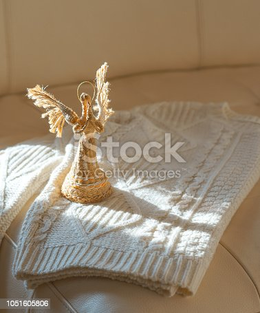 Top view to image of white cozy knitted sweater with angel in sun light on beige leather sofa background. Cozy Christmas Sweater. Warm comfortable winter clothes. Idea for Christmas gift. Copy space.