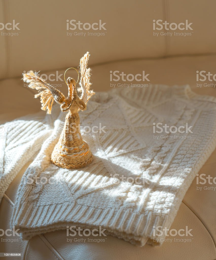 Top view to image of white cozy knitted sweater with angel in sun light on beige leather sofa background. Cozy Christmas Sweater. Warm comfortable winter clothes. Ideas for Christmas gift. Copy space. stock photo
