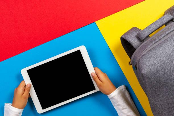 Top-Ansicht zu Kinderhänden mit Tablet-Computer und grauem Rucksack auf buntem Hintergrund – Foto