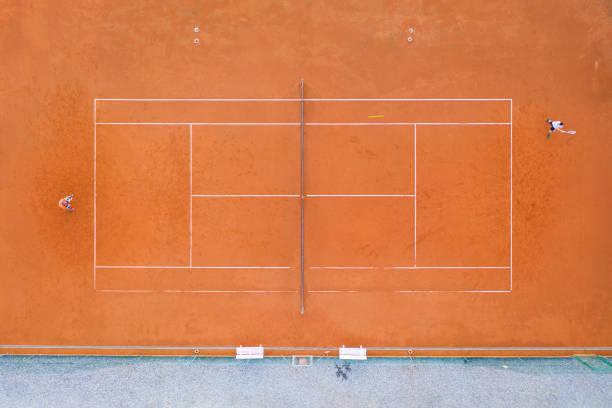 Top-Ansicht zum orangefarbenen Sandplatz, wo zwei Spieler ein Sport-Tennis-Match spielen – Foto