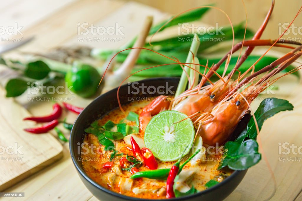 Top view 'Tom Yum Kung' on wooden background, It's local in Thai food, Prawn soup is popular and famous food, I'ts delicious amazing taste hot and spicy. stock photo