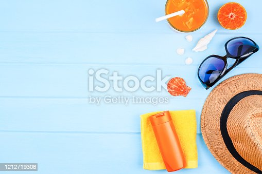 699960484 istock photo top view travel background concept with sunglasses , orange juice ,beach hat and accessories on blue wood background. 1212719308