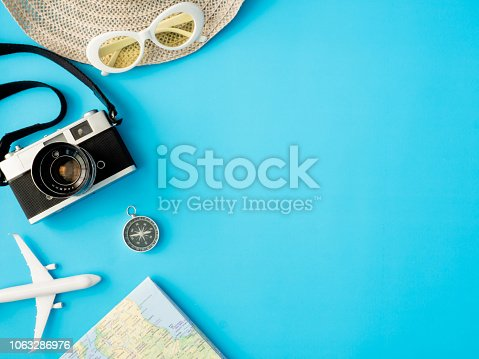istock top view travel concept with retro camera films, map, passport, smartphone on blue background with copy space, Tourist essentials, vintage tone effect 1063286976