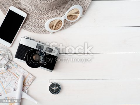 istock top view travel concept with retro camera films, map, passport, smartphone on white table background with copy space, Tourist essentials, vintage tone effect 1063287010