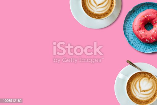 istock Top view. Two cups of fragrant delicious coffee cappuccino and a number of donut on a pink background. Nearby place for text 1006512182