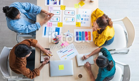 Top view ux developer and ui designer brainstorming about mobile app interface wireframe design on table with customer breif and color code at modern office.Creative digital development agency