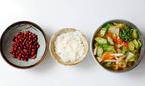Top view Vietnamese vegan cuisine, family meal, vegetables sour soup, fried peanut with soy sauce and rice bowl for lunch stock photo