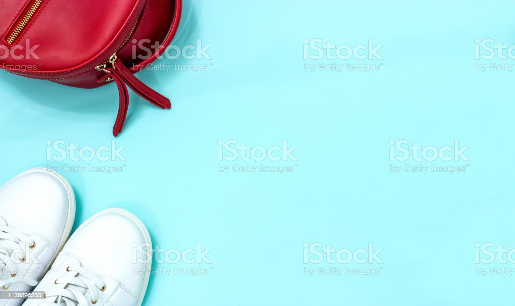 Top view White sneakers and red backpack blue background. Flat lay....