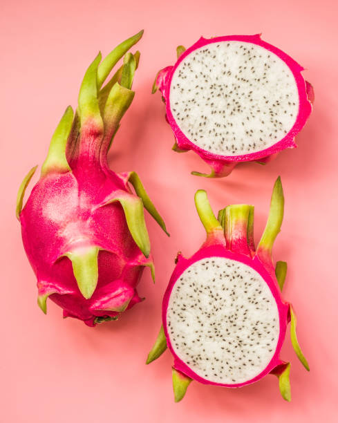top view whole and cut dragonfruit on pink background Creative layout made of pitahaya . Flat lay. Food concept. dragonfruit on pink background. pitaya stock pictures, royalty-free photos & images