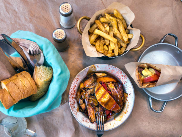 Top view with greek traditional dishes, lahanika - vegetables with cheese, pita with souvlaki, bread and fried potatoes. stock photo
