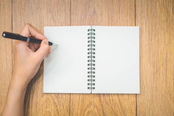 main de femme vue de dessus est écrit sur un bloc-notes vide avec un stylo sur fond de bois. - gaucher photos et images de collection