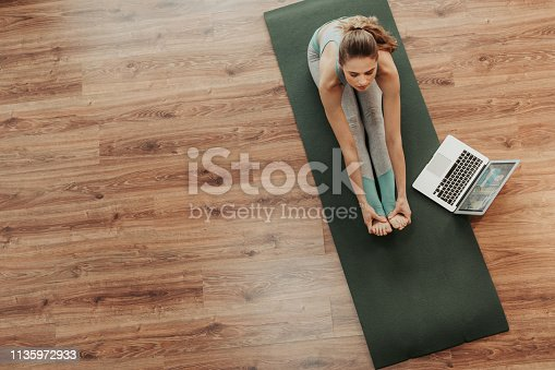 istock Top view woman in paschimottanasana yoga pose 1135972933