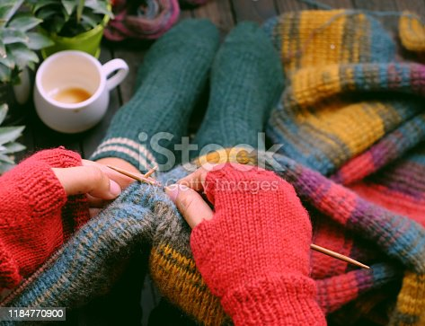 Top view woman feet with socks, sitting at home balcony, hand with knitted gloves hold knitting needle to knit colorful wool scarf  for meaningful handmade winter gift when wintertime come.