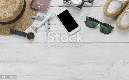 istock Top view women accessoires to travel concept.White mobile phone,airplane,hat,passport,watch,sunglasses on wood table. 837475804
