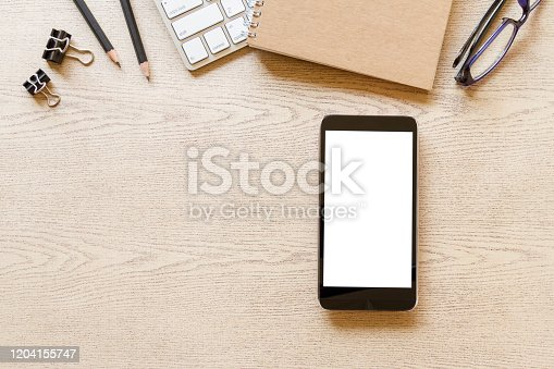 1134879628 istock photo top view wooden office desk with computer, mobile phone with blank screen, and supplies 1204155747