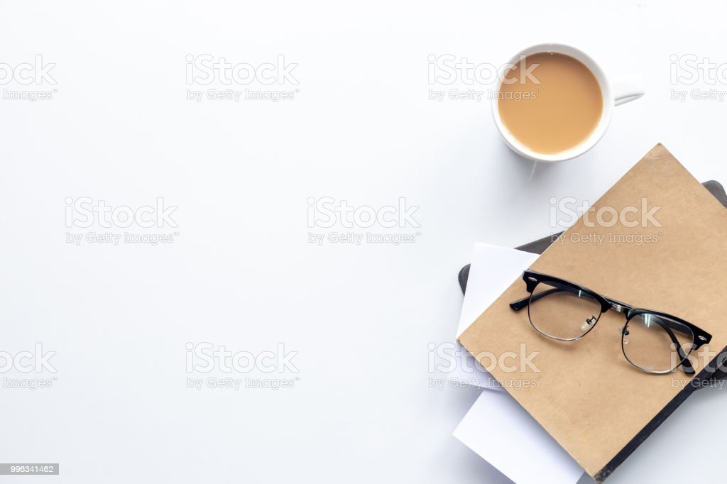 Top view workspace ,coffee cup and notebook on white table