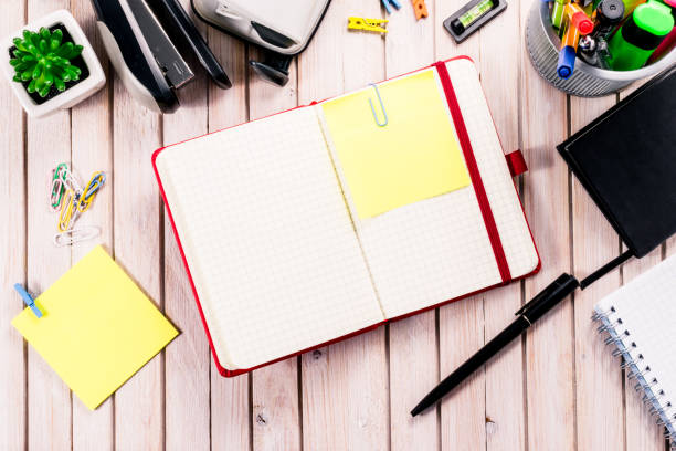 top view workspace mockup on wooden background with blank notebook with copy space, pen, tacker, punch, clips and accessories. overhead view. flat lay, top view - top view, wood table, empty imagens e fotografias de stock