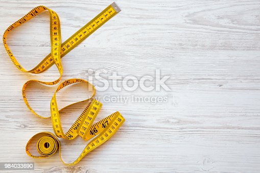 istock Top view, yellow measuring tape on white wooden background. From above. Copy space and text area. 984033690