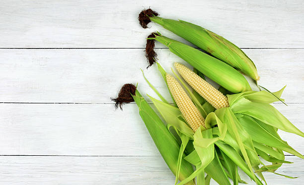 top view.Fresh sweet corn on wooden table. stock photo
