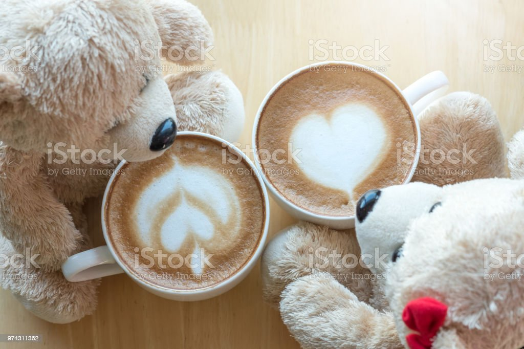 Top viwe of two teddy bears and coffee cup on pine wooden table. stock photo