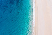 istock Top-down aerial view of a white sandy beach on the shores of a beautiful turquoise sea. 1248747102