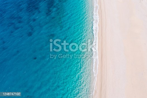 Top-down aerial view of a clean white sandy beach on the shores of a beautiful turquoise sea. Greece.