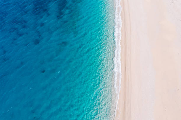 vista aérea de arriba hacia abajo de una playa de arena blanca a orillas de un hermoso mar turquesa. - playa fotografías e imágenes de stock