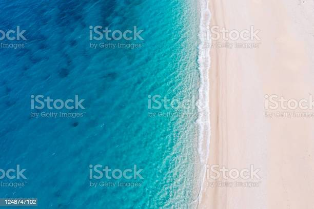 Photo of Top-down aerial view of a white sandy beach on the shores of a beautiful turquoise sea.