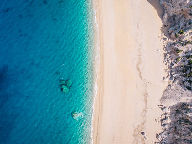 Top-down aerial view of a white sandy beach on the shores of a beautiful turquoise sea. stock photo