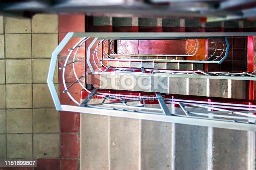 istock Top-Down View of Concrete Stairs, Metal Handrails in High-Rise Residential Building. Emergency Exit Concept. 1151899807