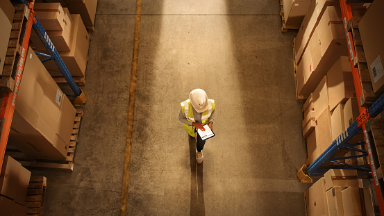 Top-Down View: Worker Wearing Hard Hat Checks Stock and Inventory Using Digital Tablet Computer in the Retail Warehouse full of Shelves with Goods. Working in Logistics, Distribution