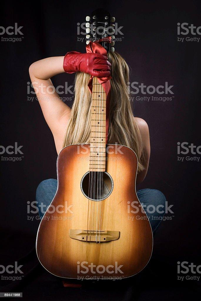 Bionda in topless in guanti rossi con chitarra foto stock royalty-free