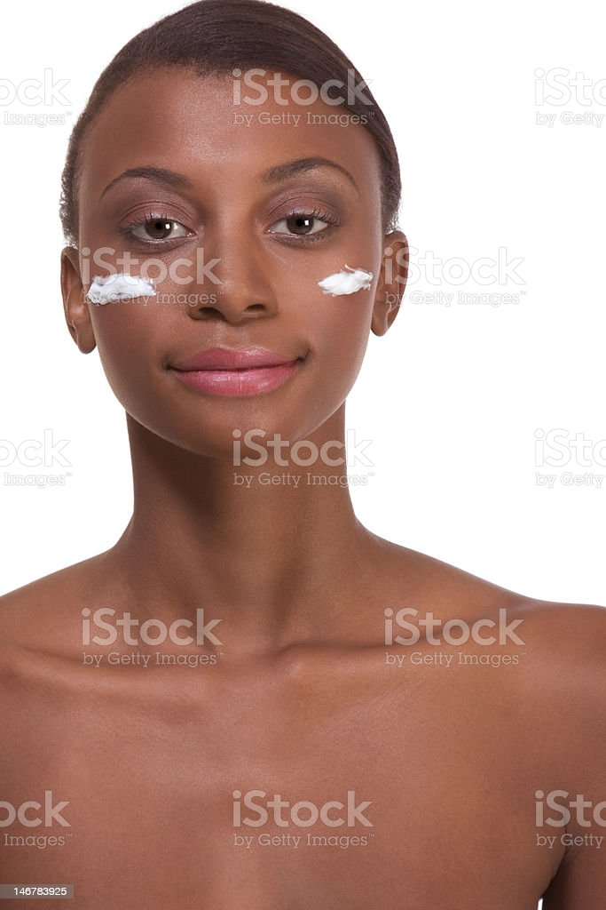 Topless ethnic Black woman moisturizing face royalty-free stock photo