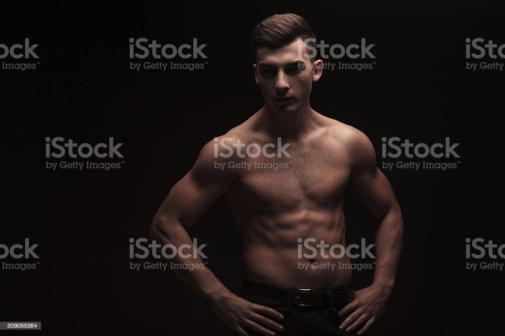 topless muscular guy posing in dark studio background stock photo