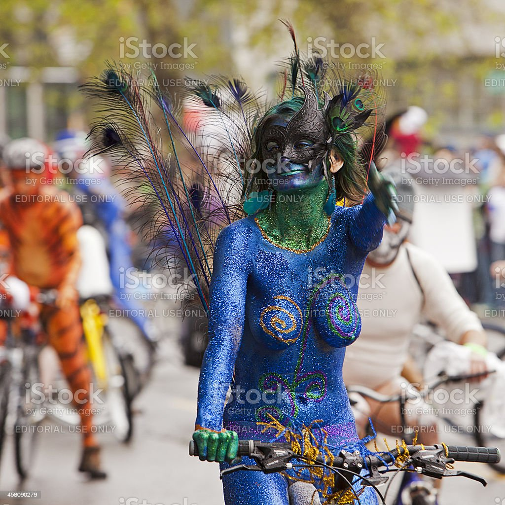 Topless Woman On Bike Is Painted As Peacock royalty-free stock photo