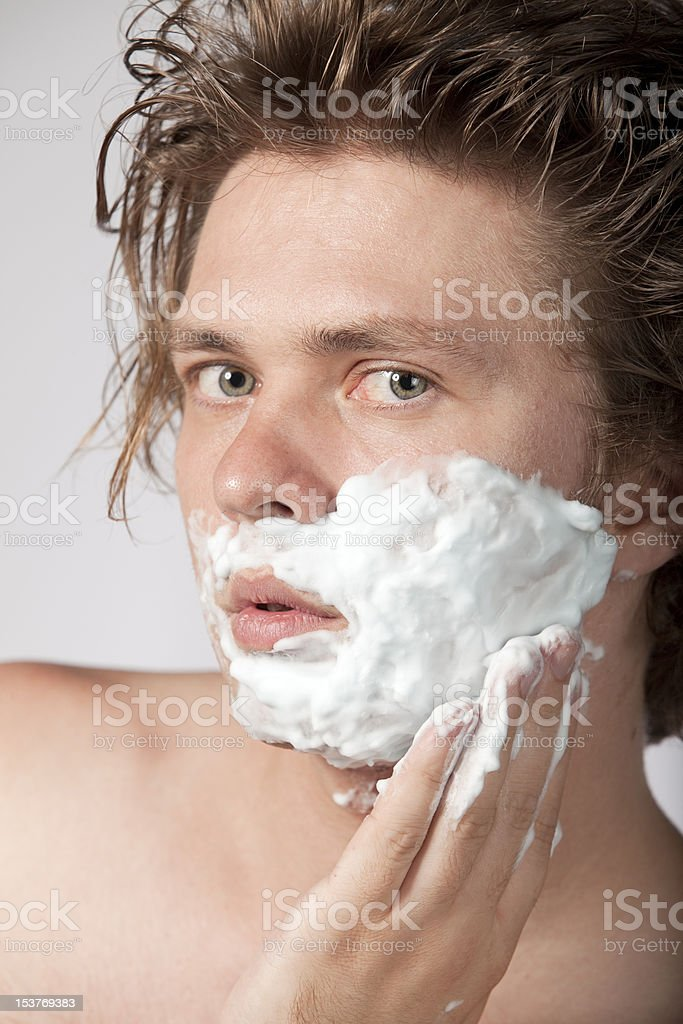 Topless young man applying shaving foam on his face royalty-free stock photo