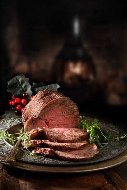 Topside Roast Beef II Succulent prime roast beef topside rump joint carved and ready for serving. Shot against a rustic, festive background with generous accommodation for copy space. roast beef stock pictures, royalty-free photos & images