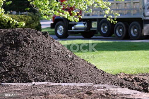 Large Dump Truck leaves residential property after delivering pile of topsoil - foreground focus with deliberate background blur.