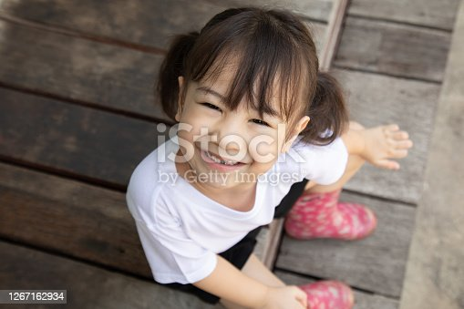 Top-view portrait of adorable Asian girl, about 4 years old with white shirt, who is looking up and smiling on the blurred background of vintage wooden floor, shows enjoyment and cheerfulness.