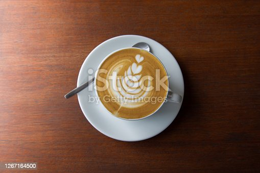 Top-view shot of single cup of latte coffee with art cream foam in white ceramic cup on wooden vintage table with sun lighting and shade in the morning after breakfast for relaxing and starting a day.