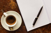 Hot coffee on the desk, Topview workspaces, black business pens with notebooks.