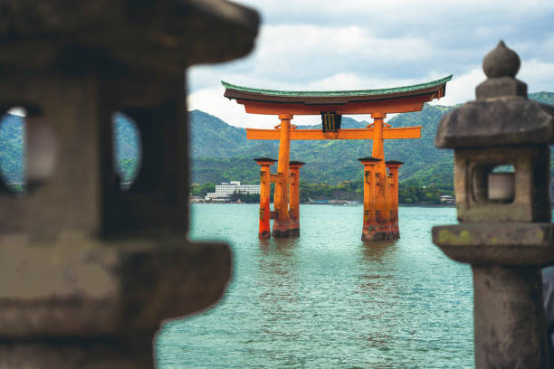 Tori gate - famous buddhist shrine near Miyajima island in Japan Itsukushima Island (Miyajima Island), Japan - April 26, 2019: Famous Tori gate in high tide of Japanese Inland Sea, on the shore of Miyajima Island. miyajima stock pictures, royalty-free photos & images