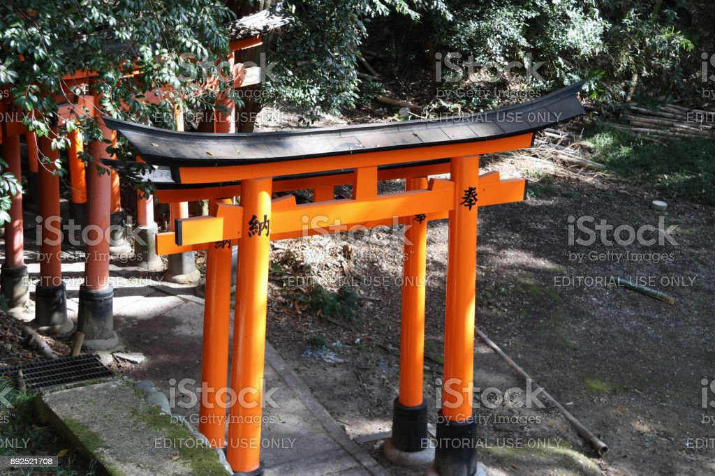 Torii and the tree background. It is a traditional Japanese gate most commonly found at the entrance of where it symbolically marks the transition from the profane to sacred. stock photo