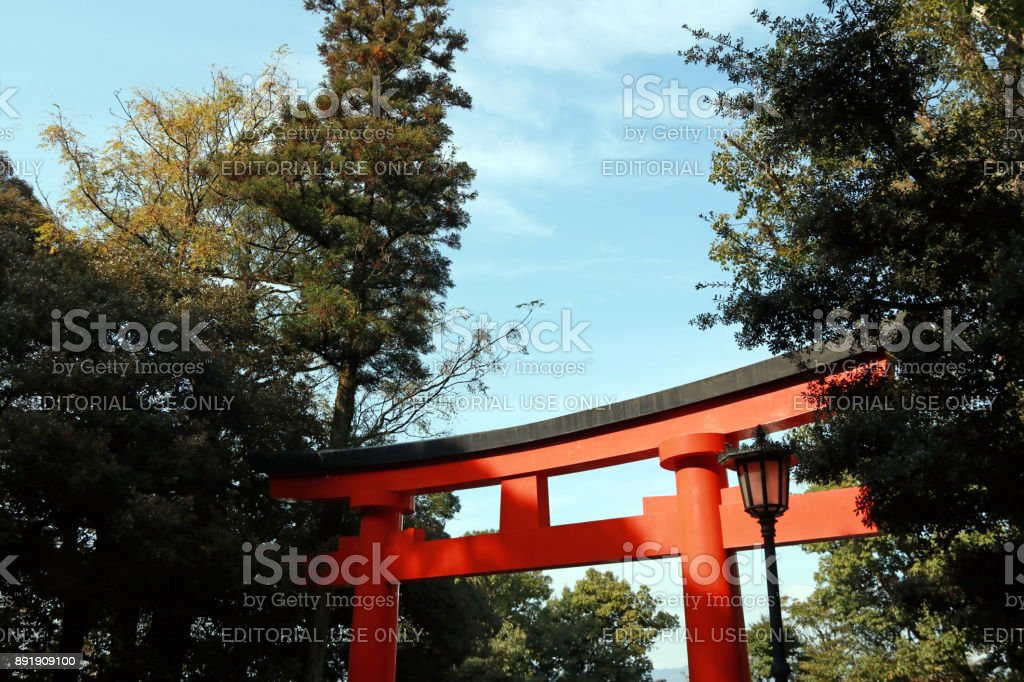 A torii and the tree with blue sky background. It is a traditional Japanese gate most commonly found at the entrance of where it symbolically marks the transition from the profane to sacred. stock photo