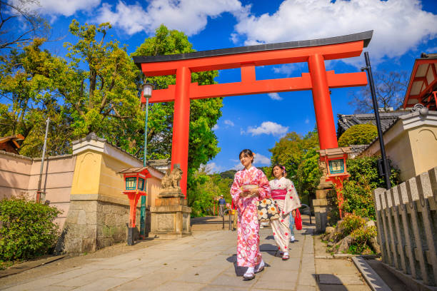 Torii Gate of Yasaka Shrine Kyoto, Japan - April 24, 2017: Japanese women in kimono cross one of red Torii Gate of Yasaka Shrine in spring season. Gion Shrine is one of most famous shrines between Gion and Higashiyama District. shinto shrine stock pictures, royalty-free photos & images
