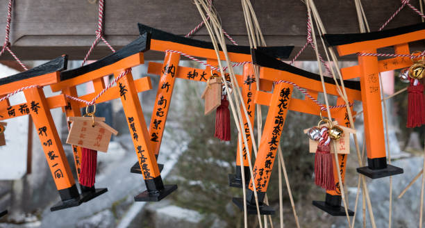 Torii-shaped Ema, Fushimi-Inari Shrine, Kyoto Kyoto, Japan - February 22, 2017 - Ema (wooden prayer plaques) shaped like miniature torii hang at a small shrine on Mt. Inari. shinto stock pictures, royalty-free photos & images